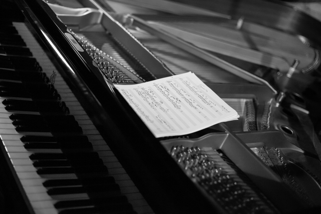 Black and white close up image of piano keyboard with sheet music