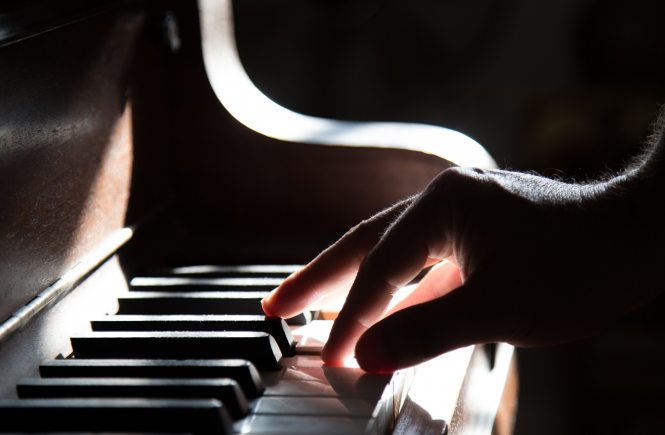 Close up image of hand playing on piano