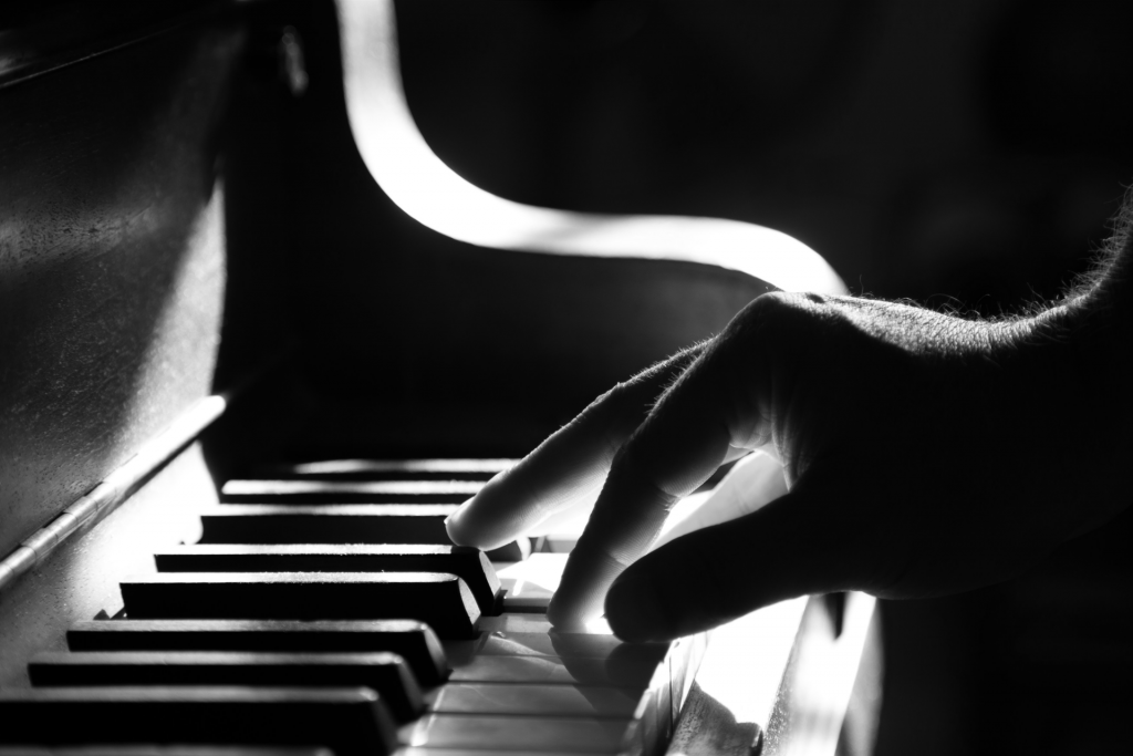 Black and white close up image of hand playing on keyboard